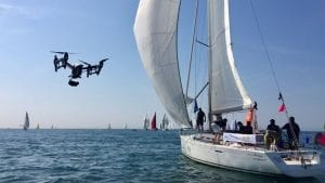 A drone with a camera flies next to a sailing yacht