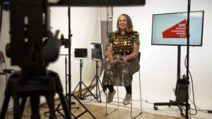 A presenter in a live studio presenting a webcast